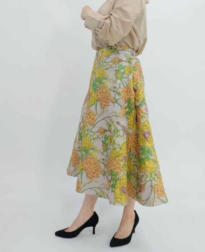 ベージュのブラウスとオレンジの花柄ジャガードスカート