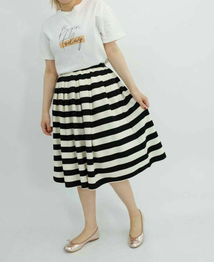 ホワイトのレタードTシャツに黒のボーダースカートでコーディネート