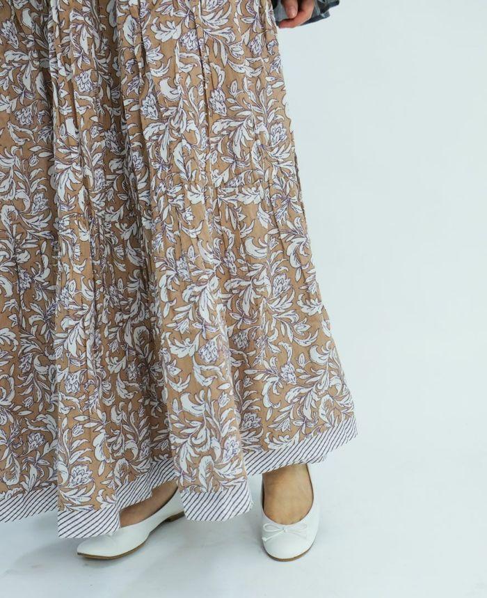 ベージュのボタニカルプリントスカートにホワイトのバレエシューズをコーディネート