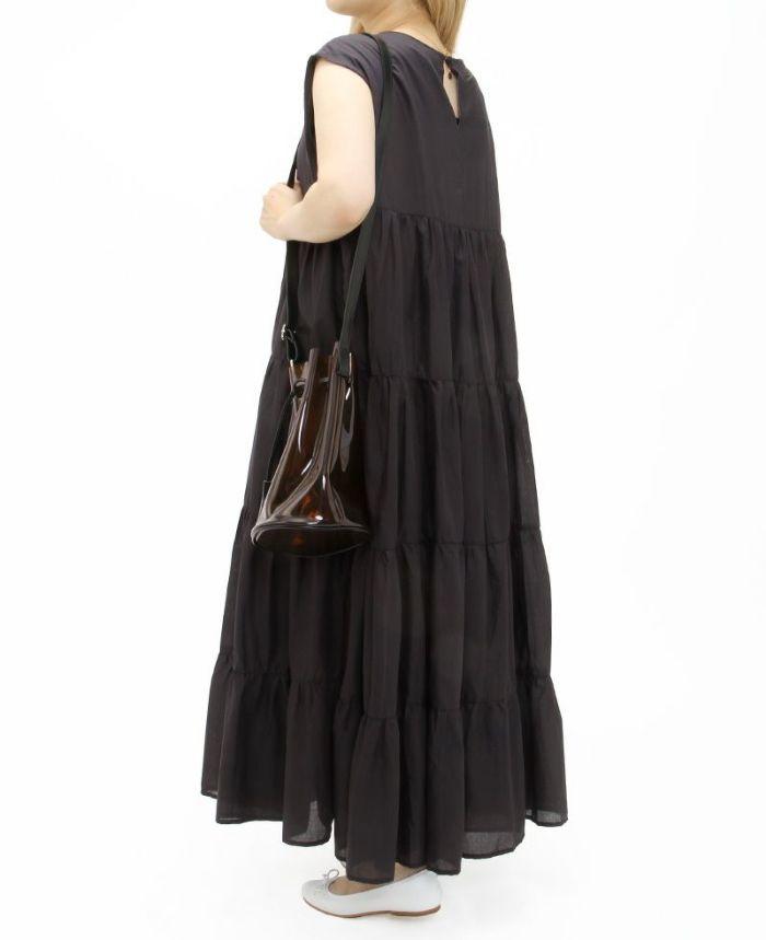 ブラックのノースリーブティアードワンピースにブラウンのクリアバッグを合わせて大人っぽく
