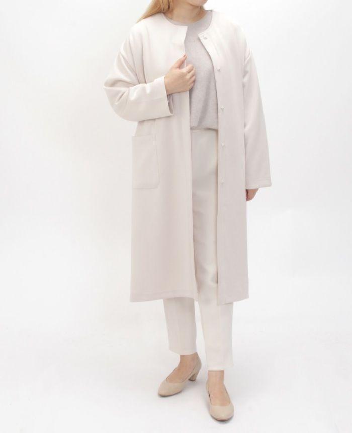 ライトダンボールコート グレージュノーカラーコートにホワイトパンツを合わせたコーディネート。