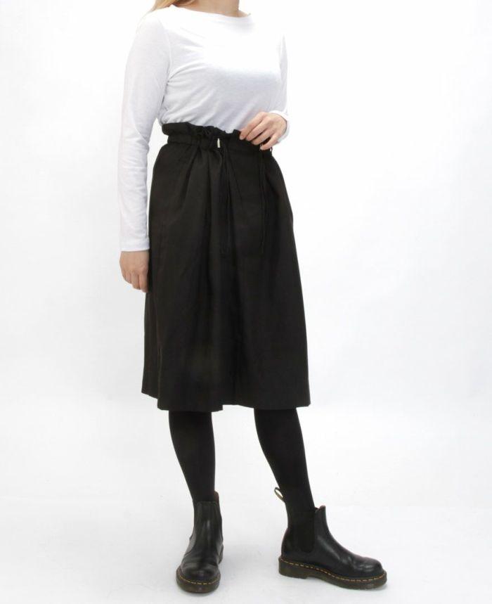 ホワイトの長袖ボートネックカットソーにブラックのスカートを合わせてモードコーデに