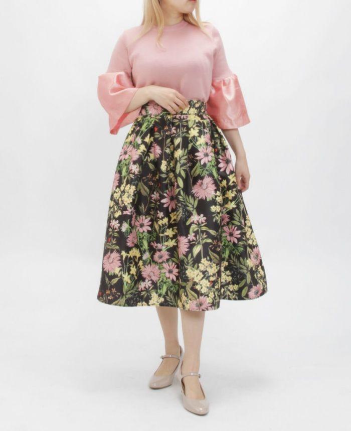 ブラックの花柄フレアスカート ピンクのラッパ袖トップス べーズのパンプス