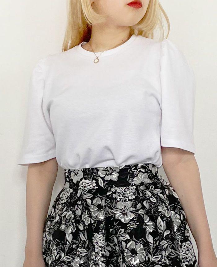 袖ボリュームトップスのホワイトと花柄スカートを着用しているバストアップ