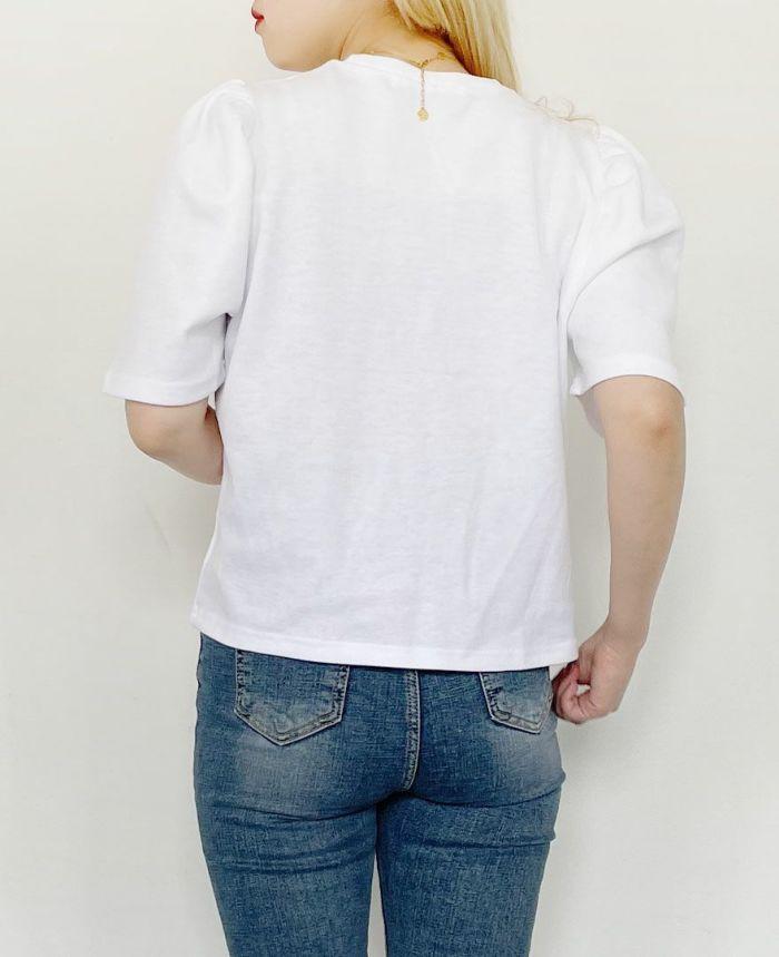 袖ボリュームトップスのホワイトとデニムパンツを着用している女性の後ろ姿
