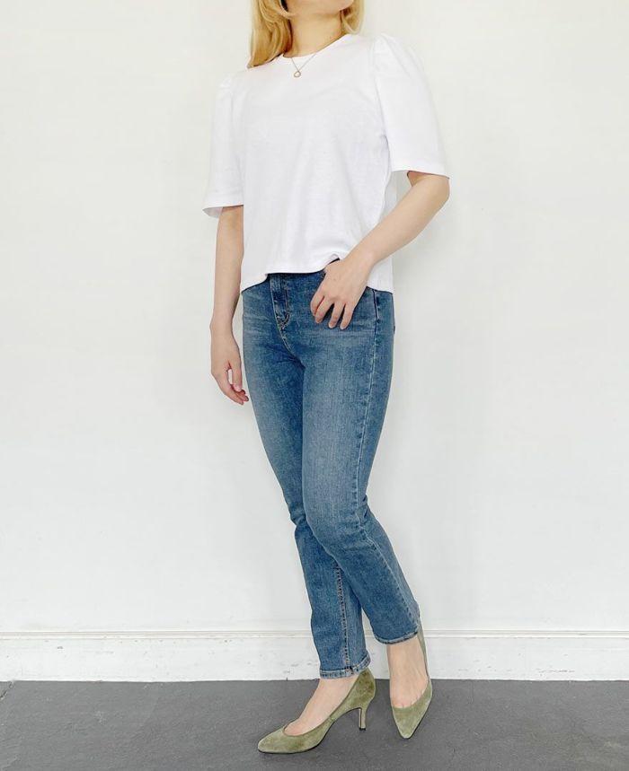 袖ボリュームトップスのホワイトとデニムパンツを着用している女性の前姿